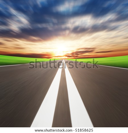 Road with motion blur and sunset. - stock photo