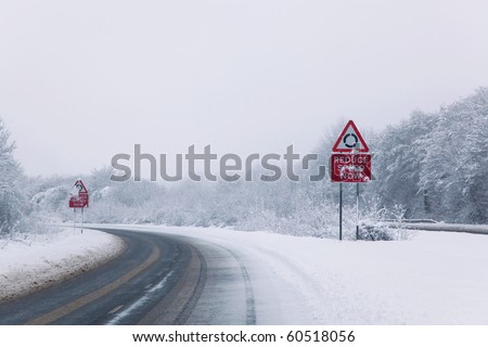 Road with Reduce speed now sign during snow fall of winter 2010 - stock photo