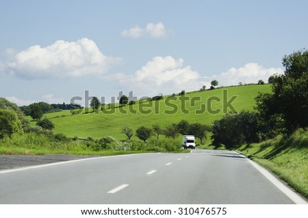 Road With Single Car in Nature Landscape - stock photo