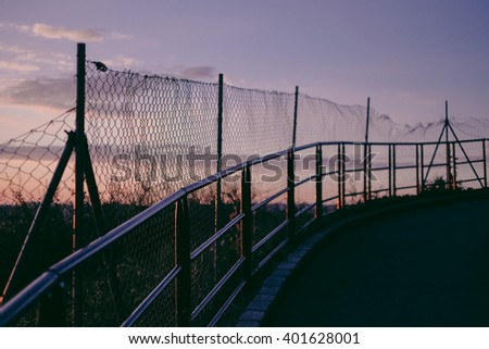 road with the fence alongside in sunset