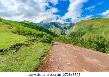 Road with tire tracks leading to mountains and beautiful clouds. Puddle with small stones on the way - stock photo