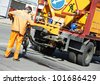 Road worker at asphalt roadway street patching reaparing work - stock photo