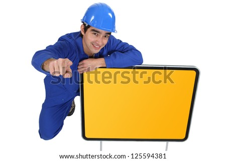 Road worker kneeling next to sign and pointing - stock photo