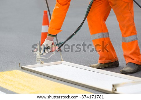 Road worker painting zebra-crossing with hand-paint gun tool - stock photo