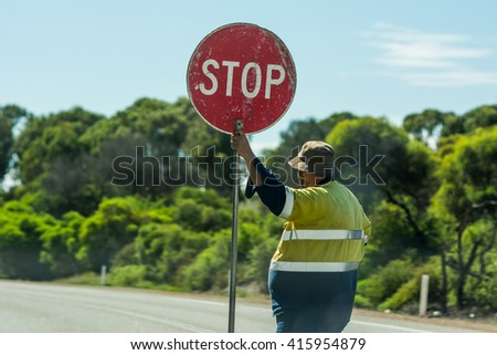 Road worker slows traffic with stop sign - stock photo