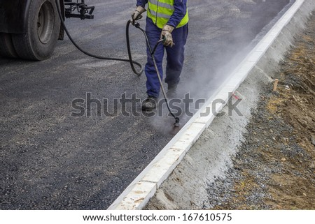 Road worker spraying bitumen emulsion with the hand spray lance - stock photo