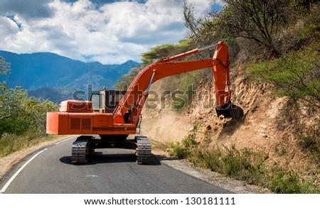Road works. Excavator repair the road. - stock photo