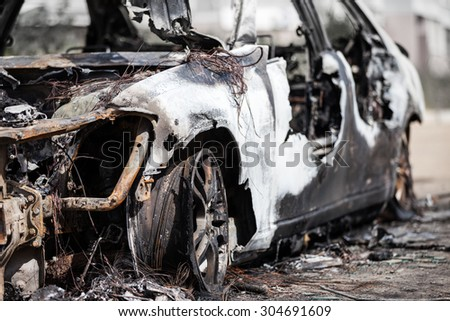 Road wreck accident or arson fire burnt wheel car vehicle junk - stock photo