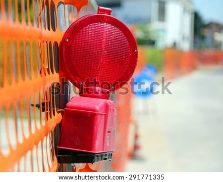 Road yard with red signal lamp on road excavation - stock photo