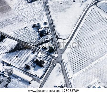 Roads crossing across fields covered in snow in winter. - stock photo