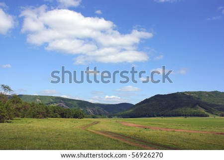Roads in the gorge. Summer landscape with mountains and blue sky and clouds