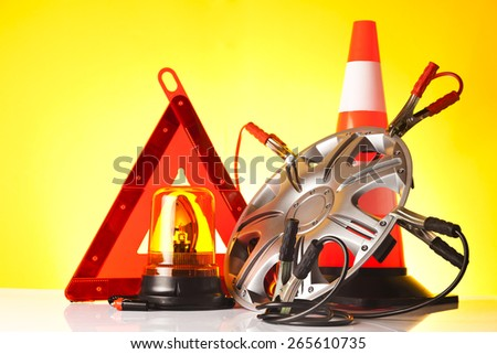 roadside assistance items and car accessories on yellow background - stock photo