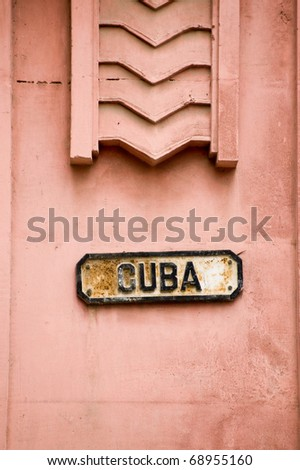 Roadsign in Havana, Cuba for a street named Cuba. Art Deco modelling above the sign.