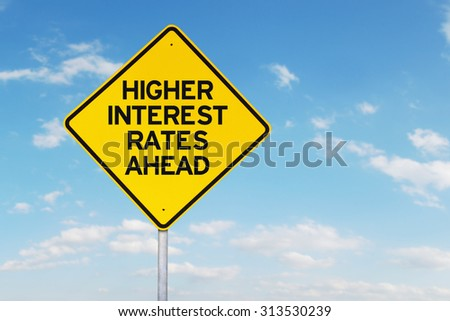 Roadsign of higher interest rates ahead against blue sky - stock photo