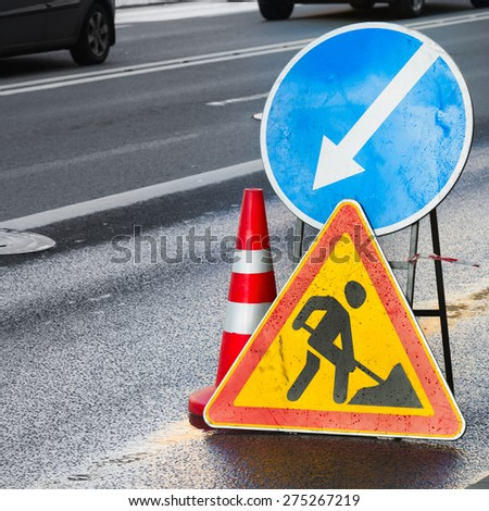 Roadsigns on the urban asphalt road. Men at work, square composition - stock photo
