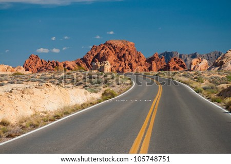 roadway in desert canyon against blue sky - stock photo