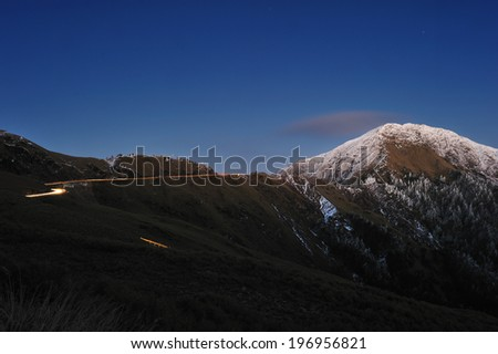 Roadway winds towards the snow capped mountain peak. - stock photo