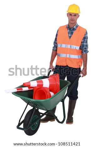 Roadworker with cones in a wheelbarrow - stock photo