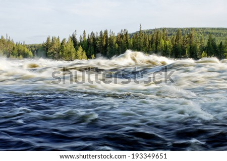 Roar from the big river. Spring and flood from the winter snow in a Nordic valley.  - stock photo