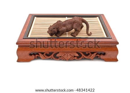 roaring tiger figurine on chinese wooden table isolated on white