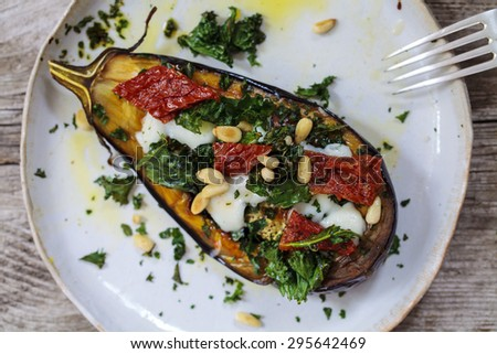 Roast aubergine with goat cheese, crispy kale, sun dried tomatoes and pine nuts - stock photo