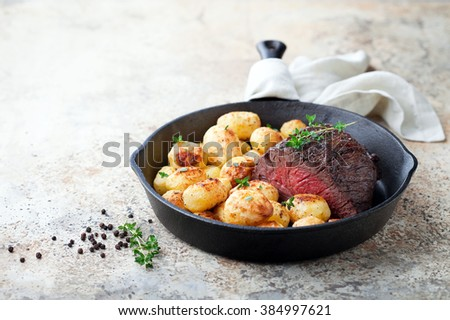 Roast beef and baked potatoes in cast iron frying pan, selective focus - stock photo