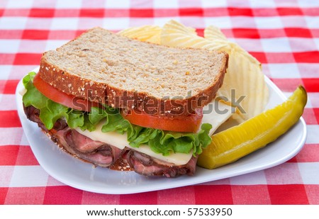 roast beef and cheese sandwich with lettuce, tomato and pickle on a classic red and white checkered background - stock photo