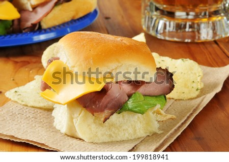 Roast beef and cheese sliders on mini buns with a mug of beer