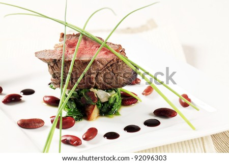 Roast beef and sauteed spinach leaves  - stock photo
