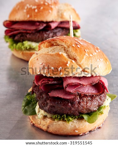 Roast beef burger on a sesame bun with gourmet sliced pastrami on a ground beef patty with lettuce on a metallic restaurant counter for a tasty takeaway snack - stock photo