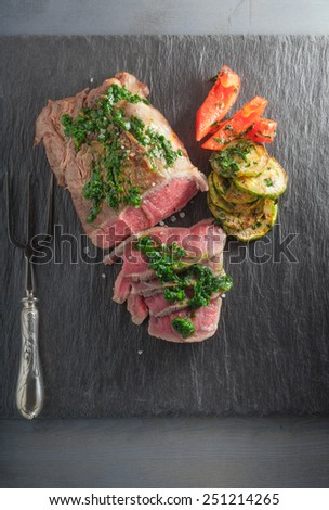 Roast Beef dinner with roasted zucchini, pepper and salsa verde - stock photo