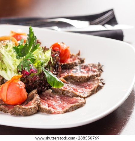 Roast beef salad with tomatoes on table at restaurant - stock photo