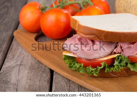 Roast beef sandwich closeup with tomato, lettuce and cheese