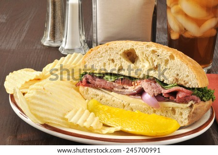 Roast beef sandwich on a ciabatta roll with potato chips - stock photo