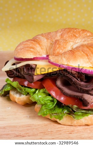 Roast beef sandwich on a croissant with cheddar and swiss cheese, tomatoes, lettuce, and onion. - stock photo