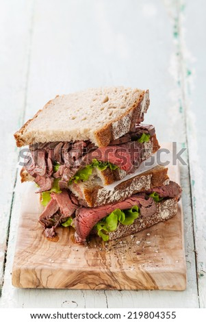 Roast beef sandwiches with lettuce on olive wood cutting board - stock photo