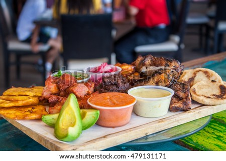Roast beef with gravy, tortillas, beans, avocado and ribs on green wood table background
