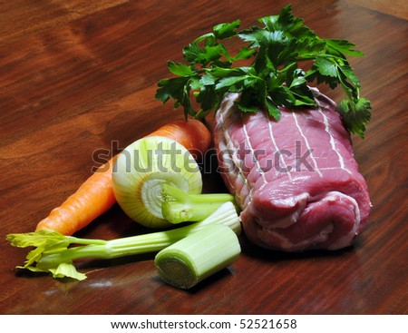 roast beef with raw carrots and parsley in a baking dish - stock photo