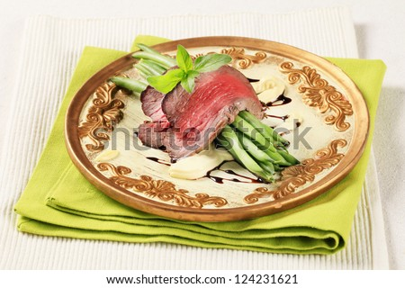 Roast beef with string green beans on a plate