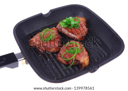 roast bloody beef fillet steaks on black grill plate with green leaves  isolated on white background