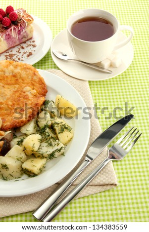 Roast chicken cutlet with boiled potatoes and  vegetables, cup of tea and dessert, on green table cloth