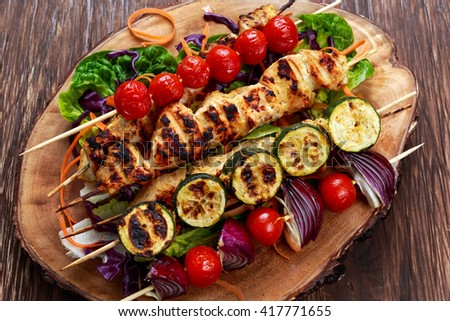 Roast Chicken filet kebab with cherry grilled on BBQ. tomatoes, zucchini and red onions on bamboo sticks. - stock photo