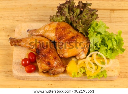 Roast chicken legs on cutting board - stock photo
