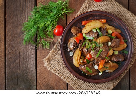 Roast chicken liver with vegetables on wooden background. Top view - stock photo