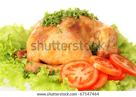Roast chicken on leaves salad on a white background is isolated.