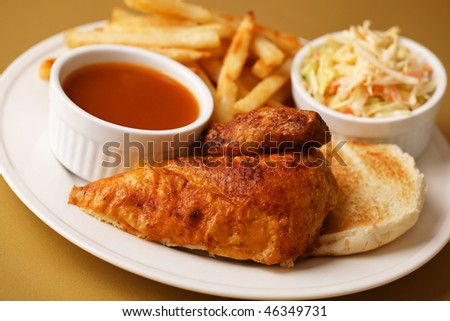Roast chicken quarter breast with french fries, cole slaw salad and bbq sauce on the side. Shallow depth of field. - stock photo