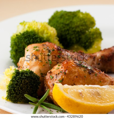 Roast chicken with broccoli and lemon - stock photo