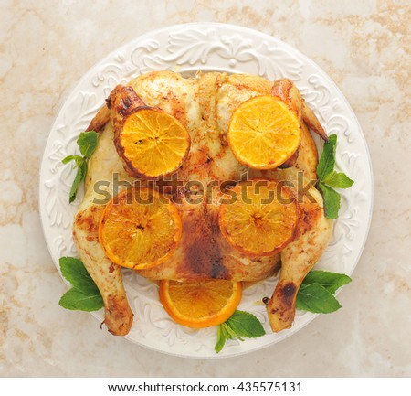 roast chicken with lemon and honey - whole chicken on a platter - top view - stock photo