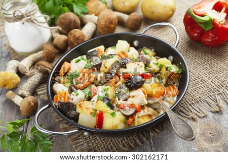 Roast chicken with potatoes and mushrooms in a frying pan