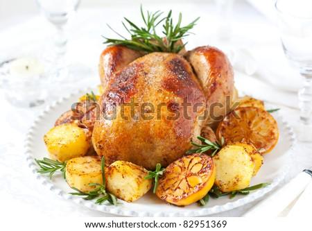 Roast chicken with potatoes,lemons and rosemary - stock photo
